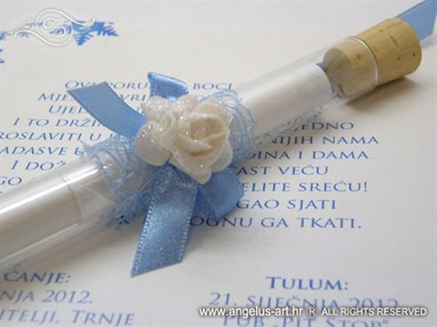 plava epruveta s pozivnicom za vjenčanje i bijelom ružom